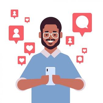 Homem afro-americano usando o aplicativo móvel em notificações de smartphone com gostos seguidores comentários retrato de conceito de vício digital de rede de mídia social