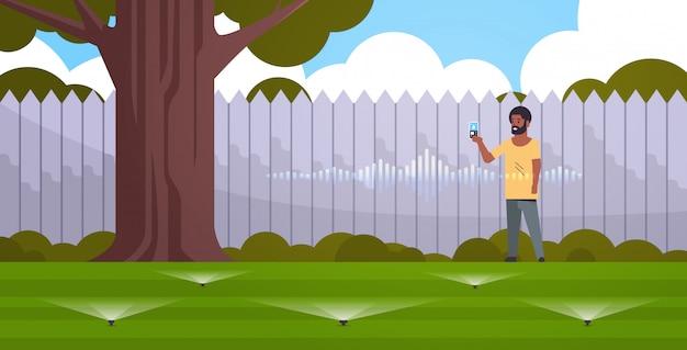 Homem afro-americano, usando o aplicativo móvel para controlar a grama de irrigação