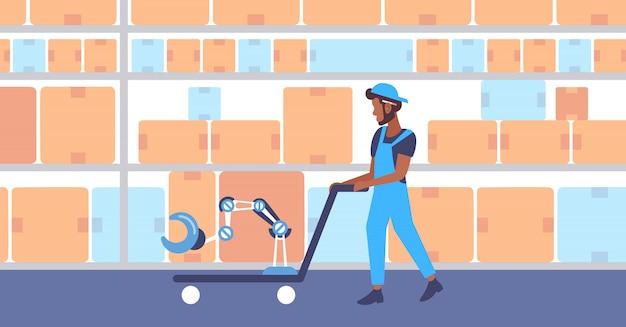 Homem americano africano, puxando, carrinho mão, caminhão, com, robotic, mecânico, braço, automático, armazém, equipamento, moderno, storehouse, interior, horizontal