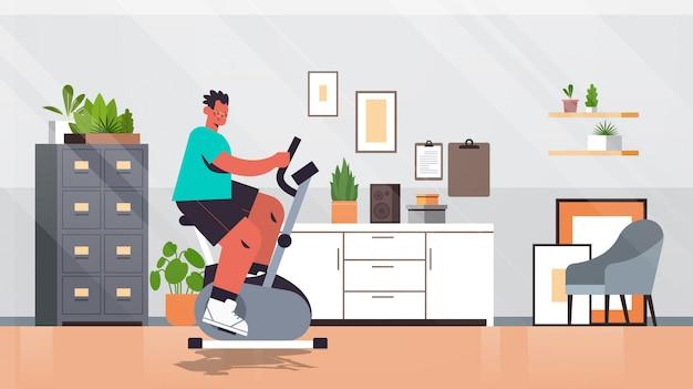 Homem andando de bicicleta estacionária em casa cara tendo treino cardio fitness treinamento estilo de vida saudável esporte conceito sala interior ilustração comprimento total