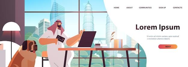 Homem árabe com cartão de crédito usando laptop conceito de compras online sala de estar interior cópia horizontal retrato ilustração vetorial