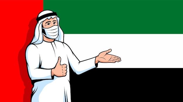 Homem árabe na máscara de fase com o polegar para cima no fundo da bandeira dos emirados árabes unidos. muçulmano durante uma pandemia