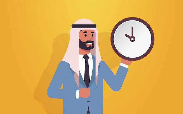 Homem árabe segurando o conceito de prazo de gerenciamento de tempo relógio homem de negócios árabe com despertador retrato de personagem de desenho animado masculino horizontal