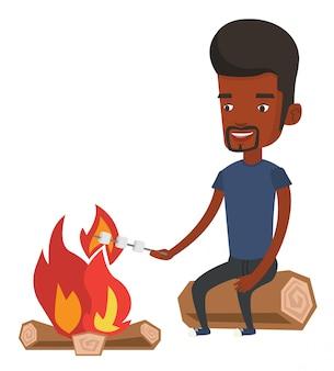 Homem assar marshmallow sobre fogueira.