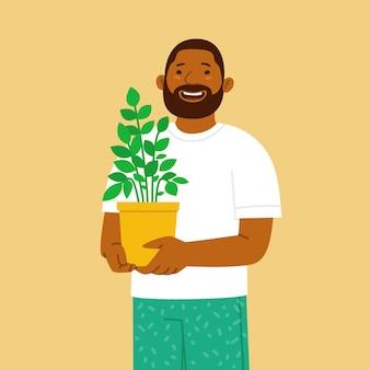Homem barbudo feliz segurando um vaso com uma planta de casa nas mãos hobby de cultivar plantas e flores