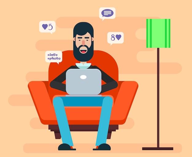 Homem barbudo sentado na poltrona com laptop