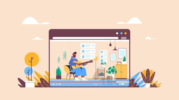 Homem blogger tocando guitarra gravando vídeo blog online streaming ao vivo conceito de blogging cara vlogger na janela do navegador da web interior da sala de estar horizontal