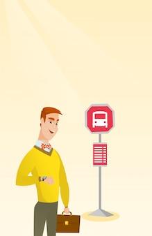 Homem caucasiano, esperando por um ônibus na parada de ônibus.