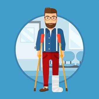 Homem com a perna quebrada e muletas.