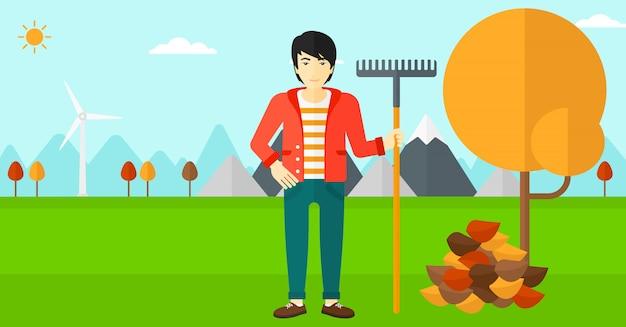 Homem com ancinho em pé perto de árvore e monte de folhas de outono