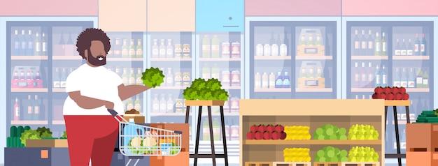Homem com carrinho carrinho escolhendo legumes e frutas cara supermercado conceito de cliente