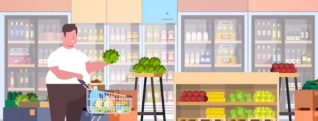 Homem com carrinho de compras escolhendo legumes e frutas cara supermercado cliente