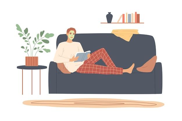 Homem com creme no rosto deita-se no sofá e lê.