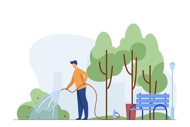 Homem com mangueira regando no parque da cidade. jardineiro, trabalhador estadual, ilustração em vetor plana serviço municipal. esverdeamento urbano, conceito de trabalho de paisagismo