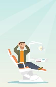 Homem com medo sentado na cadeira odontológica.