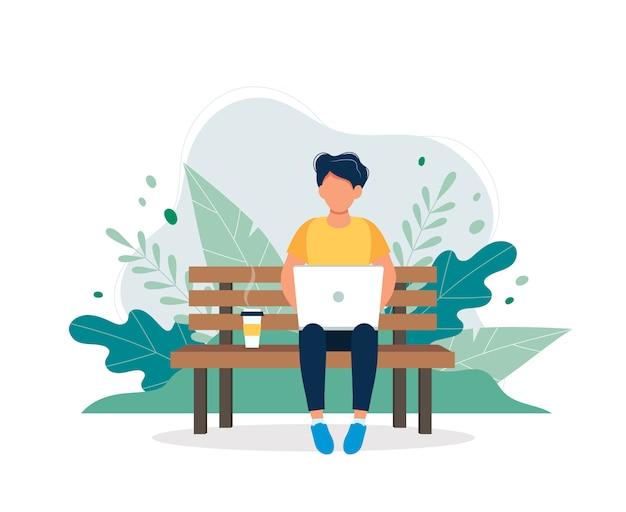 Homem com o portátil que senta-se no banco na natureza e nas folhas.