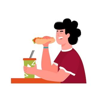 Homem comendo cachorro-quente e segurando um copo de bebida para viagem, mesa de café fast-food