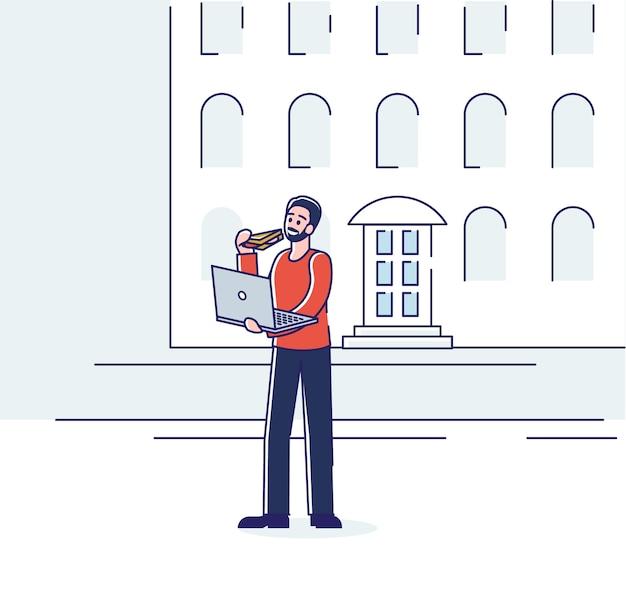 Homem comendo em movimento segurando e digitando no laptop.