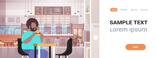 Homem comendo hambúrguer cara sentado no café mesa conceito de alimentos pouco saudáveis interior restaurante moderno