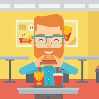 Homem comendo hambúrguer.