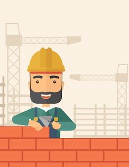Homem construtor está construindo um muro de tijolos.