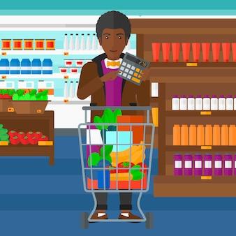 Homem contando com calculadora no supermercado