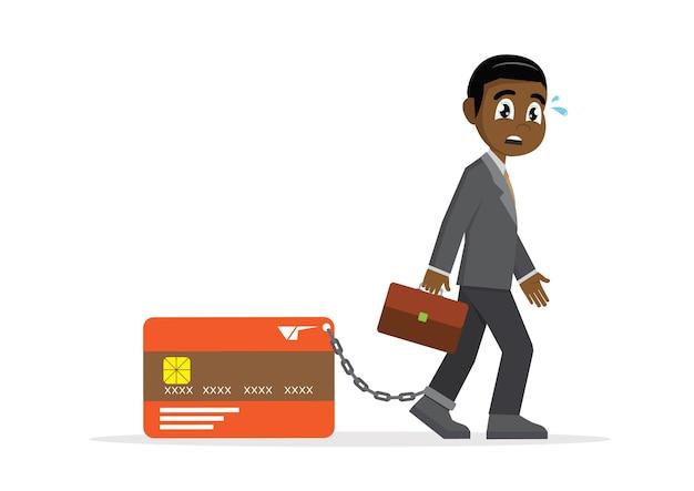 Homem de negócios africano com o pé acorrentado a depositar o cartão de crédito.