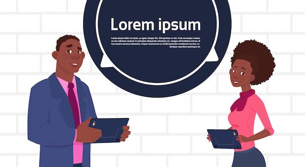 Homem de negócios americano africano e mulher segurando tablet fala grande bolha de chat com texto espaço de cópia