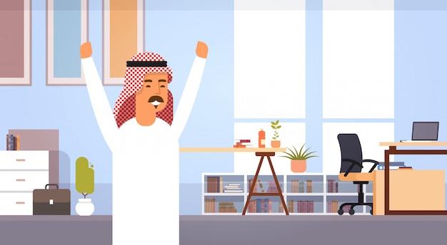 Homem de negócios árabes feliz empresário de braços erguidos no escritório moderno