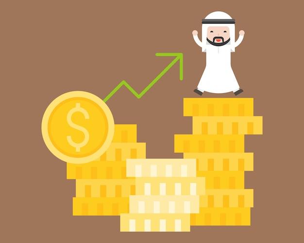 Homem de negócios árabes feliz na pilha de moedas de ouro