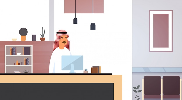 Homem de negócios árabes, usando o computador muçulmano empreendedor no escritório moderno