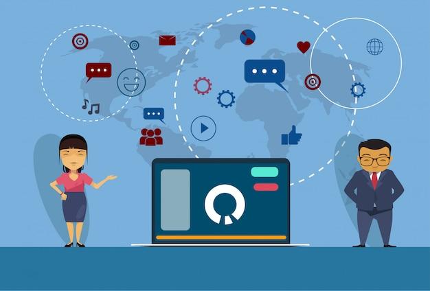 Homem de negócios asiáticos e mulher em pé no open laptop social media