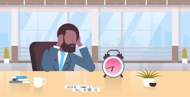 Homem de negócios cansado segurando a cabeça pelas mãos homem de negócios sentado no local de trabalho olhando o conceito de gerenciamento de tempo do despertador prazo moderno retrato interior