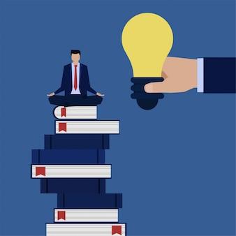 Homem de negócios conceito plana sente-se acima de livros e mão dar metáfora da idéia de obter inspiração.