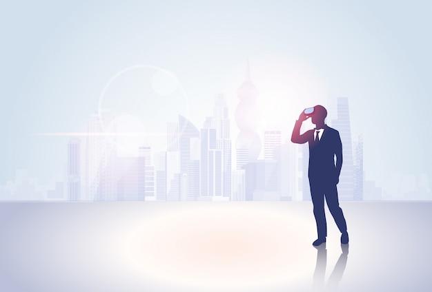 Homem de negócios de silhueta usar realidade virtual óculos digital fundo grande cidade