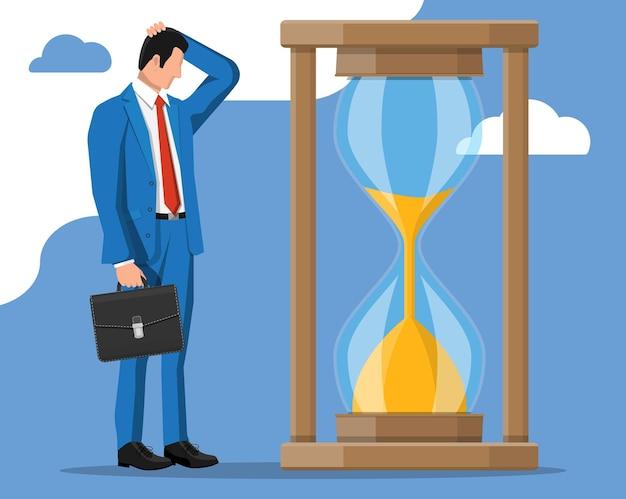 Homem de negócios desesperado perto de um relógio de ampulheta de funcionamento rápido