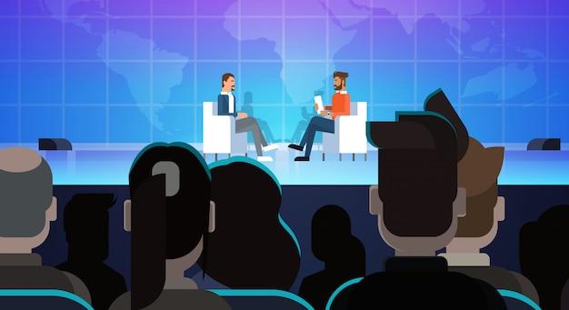 Homem de negócios na reunião de conferência de entrevista pública na frente da grande audiência
