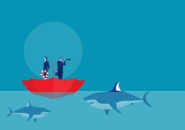 Homem de negócios que está no guarda-chuva aberto do lado de cima para baixo com a equipe cercada por tubarões.
