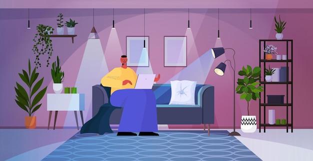 Homem de negócios sobrecarregado usando laptop no conceito de rede de mídia social de sala de estar à noite escura