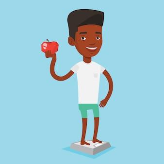 Homem de pé na balança e segurando a maçã na mão.