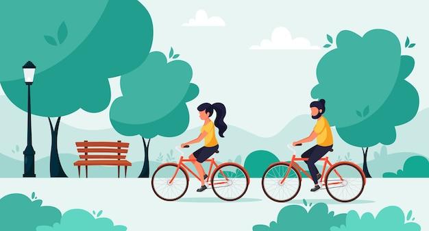 Homem e mulher andando de bicicleta no parque. o conceito de estilo de vida saudável, vida urbana. em um estilo simples.