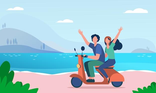 Homem e mulher andando de ciclomotor perto do rio.