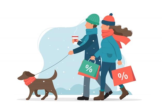 Homem e mulher com sacos de vendas, passeando com o cachorro no inverno.
