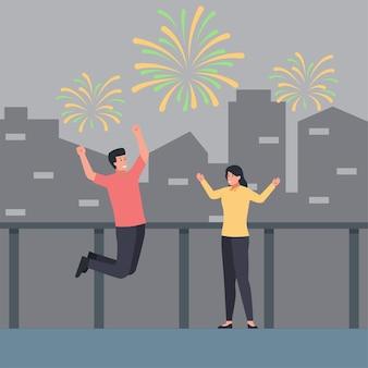 Homem e mulher comemoram e fogem de artifício no céu com a construção de plano de fundo