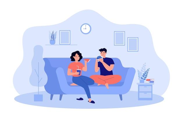Homem e mulher comendo junk food em casa. jovem casal sentado no sofá degustando uma saborosa pizza, hambúrguer