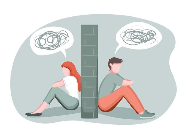 Homem e mulher deprimidos divididos por muro de pedra