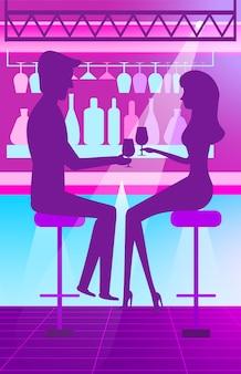 Homem e mulher em bar bebendo cocktails