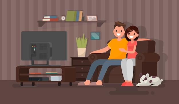 Homem e mulher sentados em frente à tv, em casa
