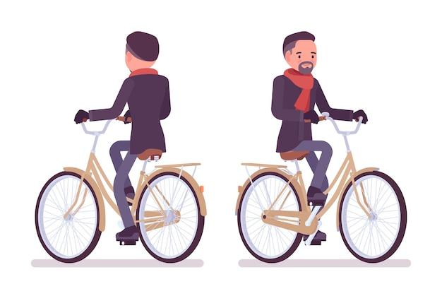 Homem elegante de meia-idade andando de bicicleta na cidade com roupas de outono.