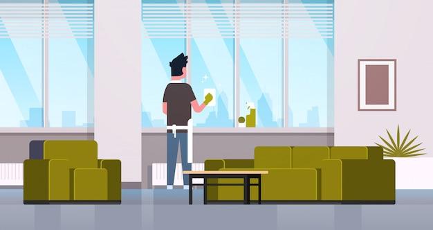 Homem em luvas e avental, limpeza de janelas com limpador de pano spray retrovisor cara fazendo o conceito de trabalho doméstico moderno apartamento sala interior